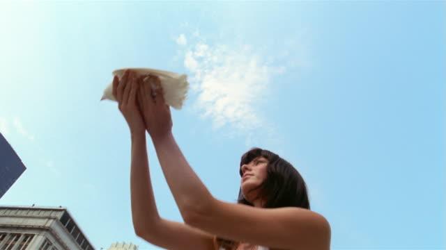 SM LA MS woman releasing dove in front of skyscrapers/ New York City