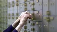 CU SELECTIVE FOCUS Woman removing and inserting safe-deposit box, Bethlehem, Pennsylvania, USA