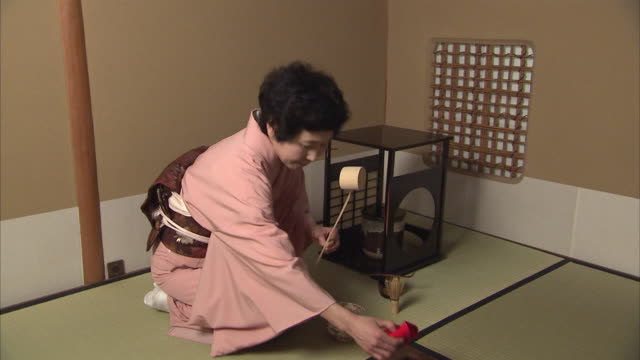 WS ZO Woman removing cover of teapot during tea ceremony, Tokyo, Japan