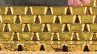 CU Woman removing gold ingots from stack / Hanau, Hessen, Germany