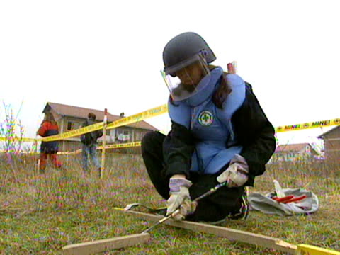 Woman removing landmines from sealedoff area