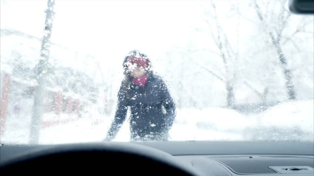 Woman removing snow from a car.