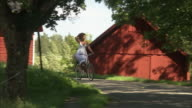 A woman riding a bike in the Swedish countryside.