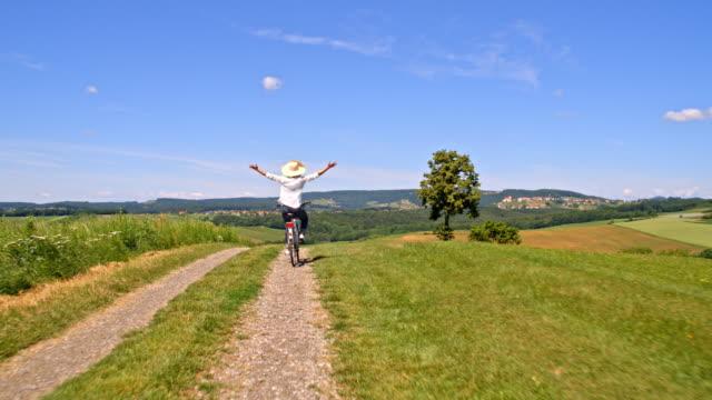 SLO MO vrouw haar fiets rijden met uitgestrekte armen