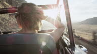 MS woman riding in passenger seat looking at man driving convertible off road vehicle on rural desert road smiling