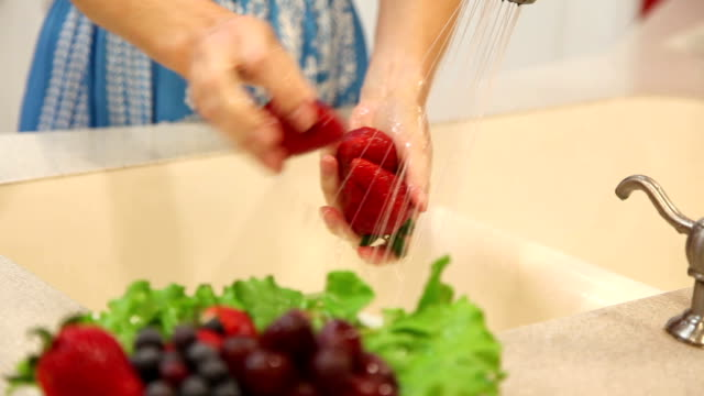 Woman rinses strawberry fruits in home kitchen sink.