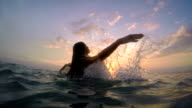 Woman rises from sea at sunset