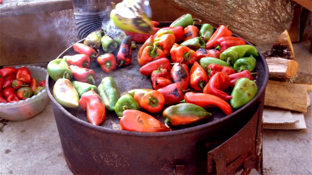 Woman roasting red and green peppers