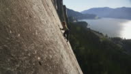 WS HA Woman rock climbing on cliff with coastline in background, Squamish, British Columbia, Canada
