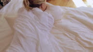 Woman rolling in bed with pillow
