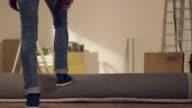 Donna lanciando tappeto in un nuovo appartamento