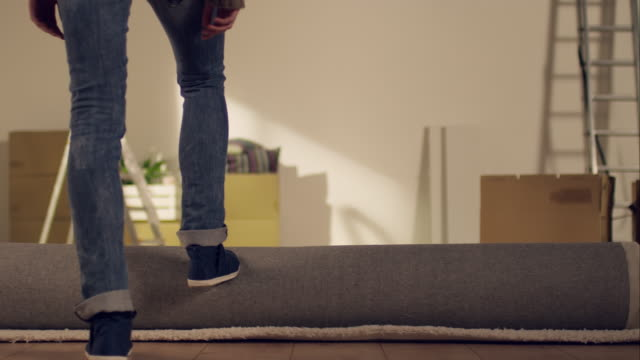 Woman rolling out carpet in new apartment