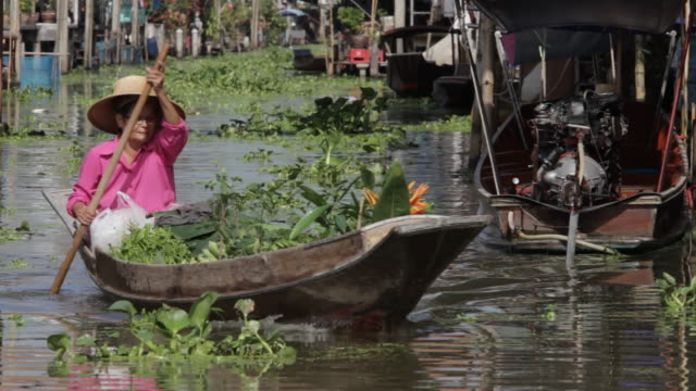 WS Woman rowing boat in floating market with fullof vegitable  products / Bangkok, Thailand