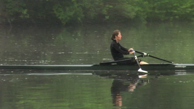 WS PAN Woman rowing in single scull on the Connecticut River at dawn/ Hanover, New Hampshire, USA