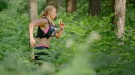 SLO MO DS Woman running a marathon through forest