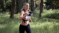 SLO MO DS Woman running a trail marathon amongst the forest trees