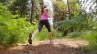 SLO MO DS Woman running across a forest clearing in sunshine