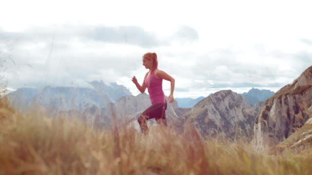 SLO MO DS Woman running across a meadow overlooking the mountains