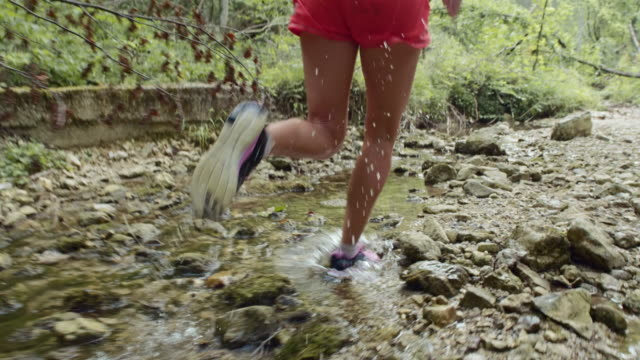 SLO MO Woman running across puddles in the creek bed
