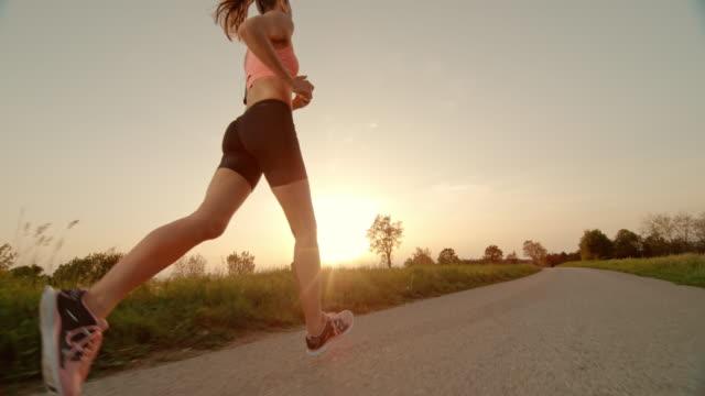 SLO MO TS TU Woman running as sun is setting