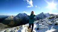 Woman running cross-country, spectacular mountains scenery