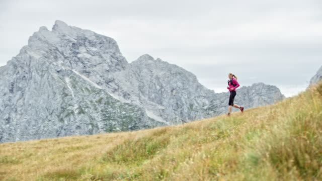 DS Woman running down a grassy ridge overlooking the nearby mountains