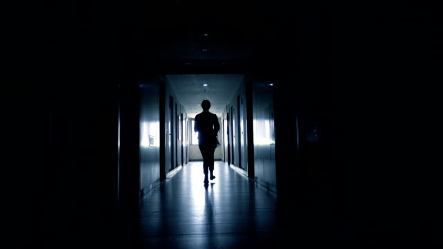 woman running in black corridor
