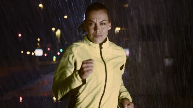 SLO MO TS Woman running in the city on a rainy night