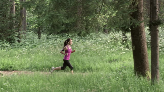 SLO MO DS Woman running on a forest trail