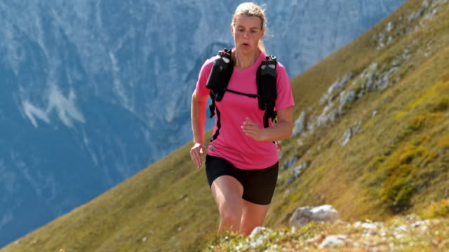 SLO MO Woman running on a grassy mountain trail in sunshine