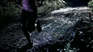 SLO MO DS Woman running on a muddy forest trail at night