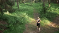 AERIAL Woman running on a path through forest