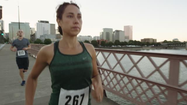 UHD 4K: SLO MO kvinna kör på bron med vackra stadsbilden i bakgrunden