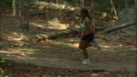 Woman running on trail through woods / Red Top Mountain State Park, Georgia