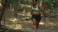 Woman running on trail through woods / running around tree past camera / Red Top Mountain State Park, Georgia