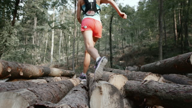 SLO MO DS Woman running over a log stack in the forest