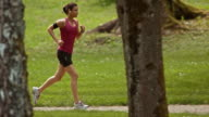 SLO MO TS Woman running through a park listening to music