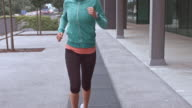 SLO MO TS Woman running through city in the morning