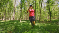 SLO MO Woman running through fern plants