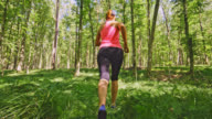 SLO MO Woman running through the forest covered with fern