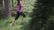 SLO MO DS TU Woman running through the forest