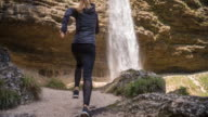 Woman running toward waterfall and stopping in front of it