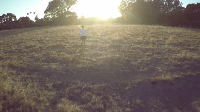 AERIAL TRACKING woman running towards sun in field
