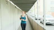 Woman running under covered sidewalk in city