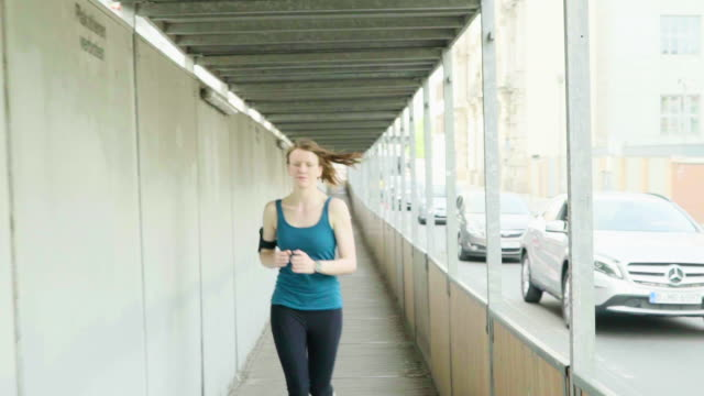 Woman running under covered sidewalk in city