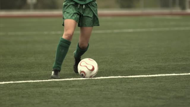 SLO MO MS PAN Woman running with and kicking soccer ball across field at Biola University / La Mirada, California, USA