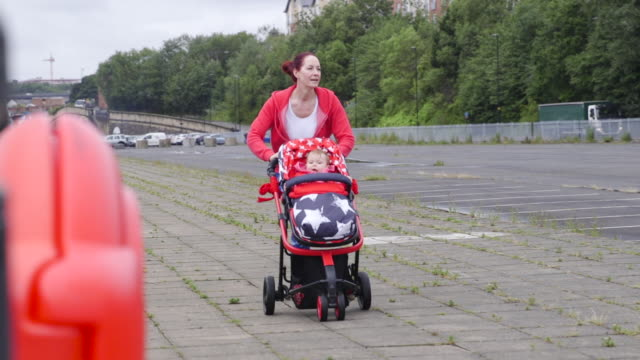 Woman Running with Her Baby Carriage on Sidewalk