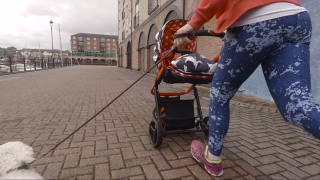 Woman Running with her Dog and Baby