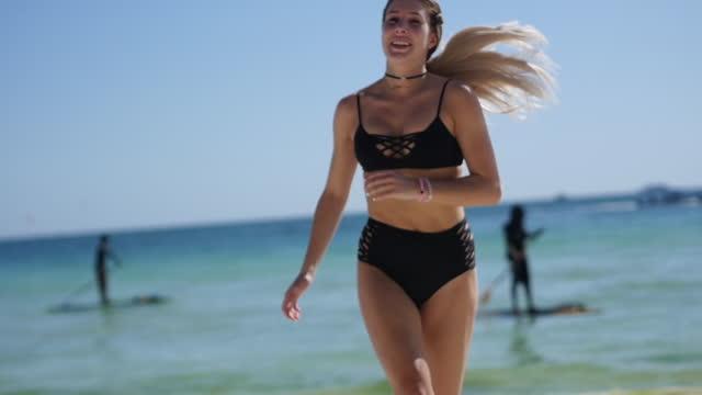 Woman runs along beach, in tropics