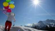 Woman runs along snowy mountain crest holding balloons